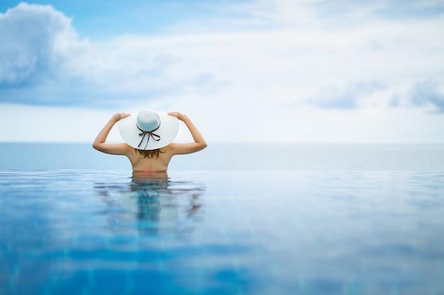 Azjatycka kobieta relaksuje w basenie na plaży Premium Zdjęcia