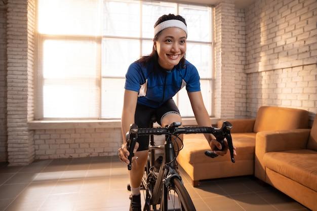 Azjatycka Kobieta Rowerzysta. ćwiczy W Domu, Jeżdżąc Na Rowerze Na Trenerze Darmowe Zdjęcia