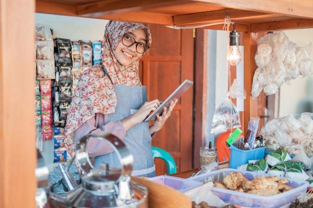 Azjatycka Kobieta Sprzedająca Angkringan W Hidżabie I Fartuchu Za Pomocą Komputera Typu Tablet, Stojącego Z Boku Boksu Wózka Premium Zdjęcia
