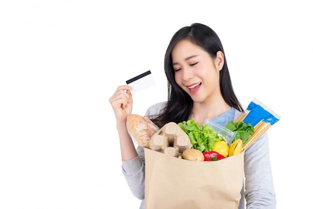 Azjatycka kobieta używa kredytową kartę dla warzywa i sklepu spożywczego zakupy Premium Zdjęcia