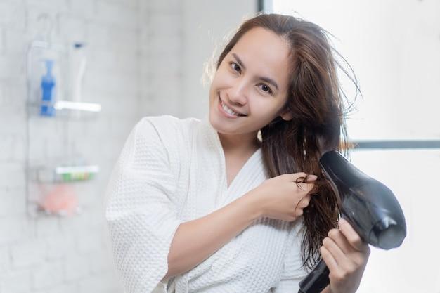 Azjatycka Kobieta Używa Suszarki Do Włosów Po Prysznicu W łazience Darmowe Zdjęcia