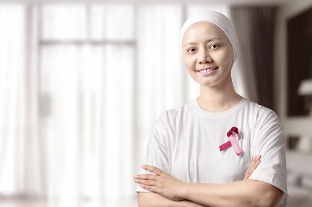 Azjatycka kobieta w białej koszula z różowym faborkiem na domu Premium Zdjęcia