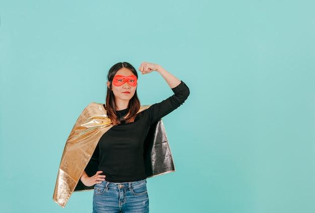 Azjatycka kobieta w bohatera kostiumu pokazuje bicepsy Darmowe Zdjęcia