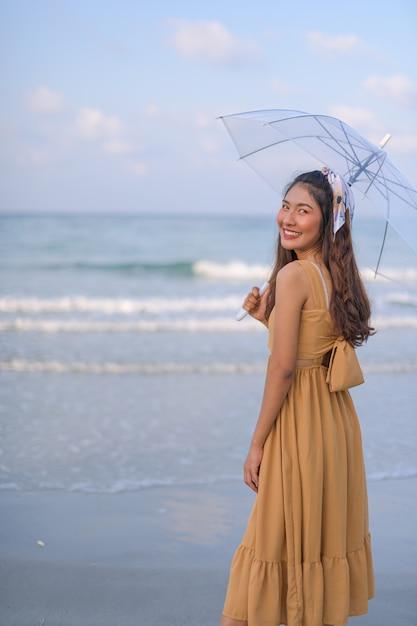 Azjatycka Kobieta W Brązowej Sukni Relaksuje Się Szczęśliwy. Z Wycieczką Na Plażę Premium Zdjęcia
