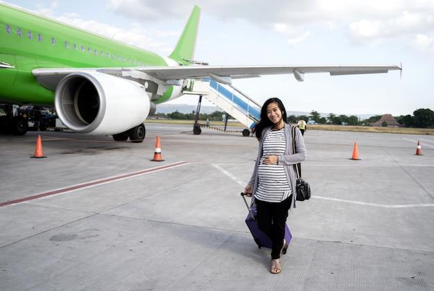Azjatycka Kobieta W Ciąży Ciągnięcia Walizki Ciągnięcie Premium Zdjęcia