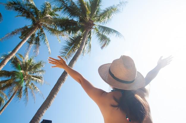 Azjatycka kobieta z słońce kapeluszem podnosił ręki z drzewkami palmowymi i niebem. letnia podróż. pojęcie wolności Premium Zdjęcia