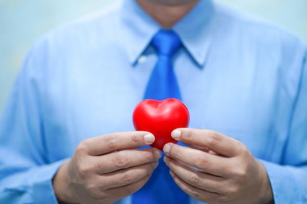 Azjatycka Mądrze Mężczyzna Lekarka Trzyma Czerwonego Serce: Zdrowy Silny Medyczny Pojęcie. Premium Zdjęcia