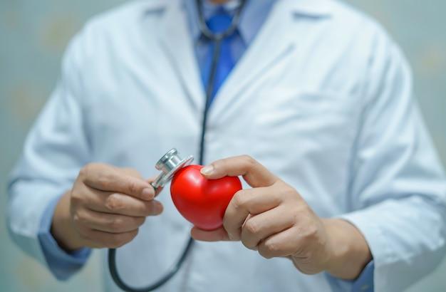 Azjatycka Mądrze Mężczyzna Lekarka Trzyma Czerwonego Serce Premium Zdjęcia