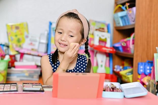 Azjatycka Mała Dziewczynka Stosuje Matka Makijaż I Maluje Twarz Kosmetykami W Domu Premium Zdjęcia