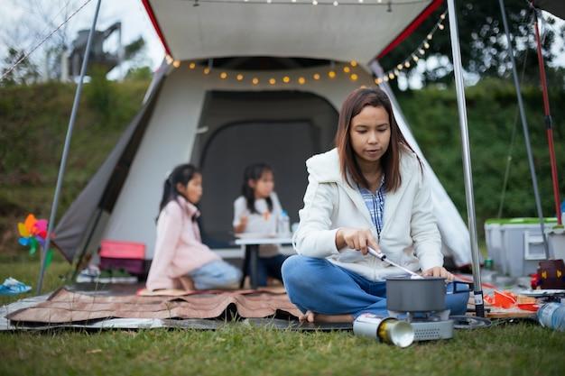 Azjatycka Matka Gotuje Dla Rodziny Poza Namiotem Podczas Biwakowania Z Rodziną Na Kempingu Ze Szczęściem. Premium Zdjęcia