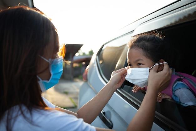 Azjatycka Matka Pomaga Córce W Noszeniu Maski Ochronnej, Aby Chronić Przed Epidemią Koronawirusa Covid-19 Przed Pójściem Do Szkoły. Przygotuj Się Do Koncepcji Szkoły. Premium Zdjęcia