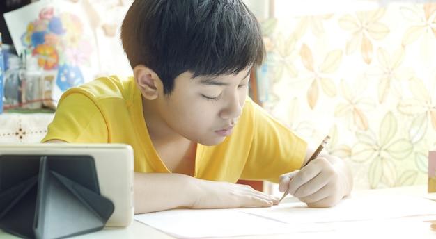 Azjatycka Matka Pomaga Jej Syna Robić Pracie Domowej Na Białym Stole. Premium Zdjęcia