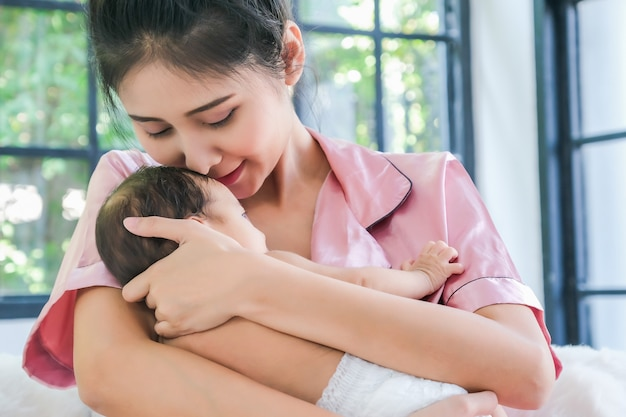 Azjatycka Matka Trzyma 1,5-miesięczne Dziecko, Pochylając Się Przez Ramię Premium Zdjęcia