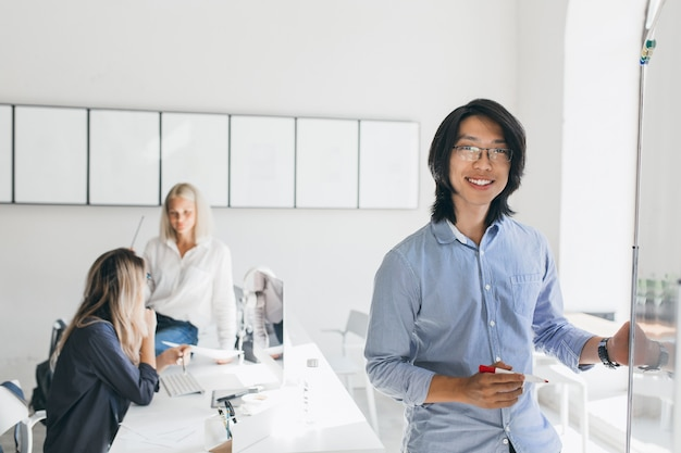Azjatycka Menadżerka Ze Szczerym Uśmiechem Pozuje Obok Flipcharta, Podczas Gdy Dziewczyny Mówią Darmowe Zdjęcia