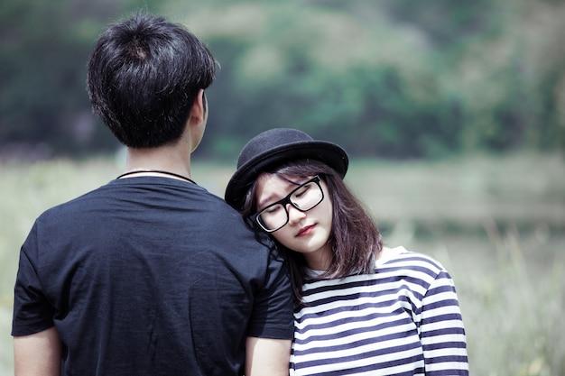 Azjatycka młoda kobieta odpoczywa na ramieniu swojego chłopaka z miłością na zewnątrz Premium Zdjęcia