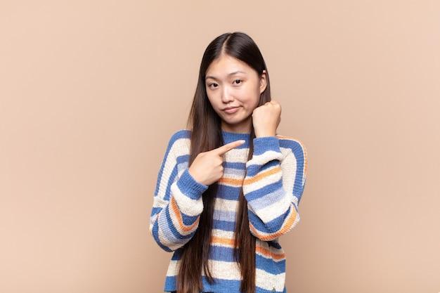 Azjatycka Młoda Kobieta Szuka Niecierpliwy I Zły, Wskazując Na Zegarek Premium Zdjęcia