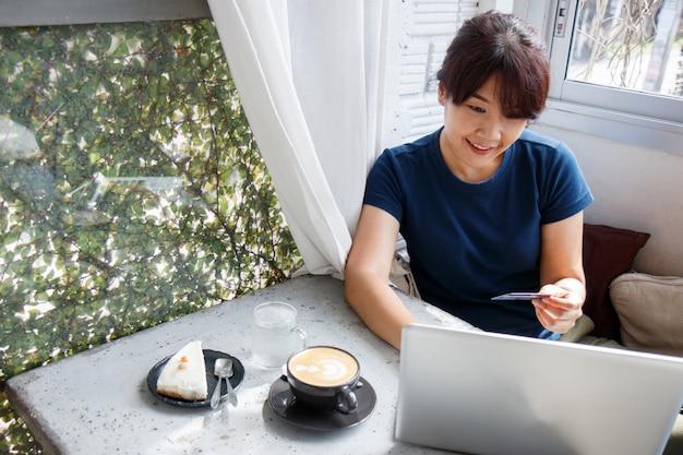 Azjatycka młoda kobieta trzyma mockup karty kredytowej i używa laptop Premium Zdjęcia