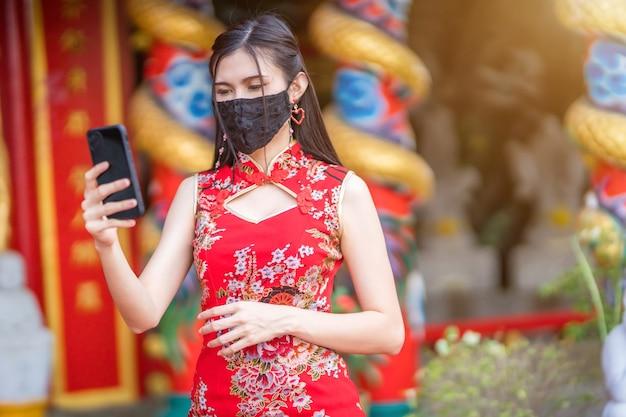 Azjatycka Młoda Kobieta Ubrana W Czerwony Tradycyjny Chiński Cheongsam I Nosi Maskę Ochronną I Smartfon Na Obchody Chińskiego Nowego Roku W Sanktuarium, Zapobieganie Rozprzestrzenianiu Się Wirusa Covid-19 Premium Zdjęcia