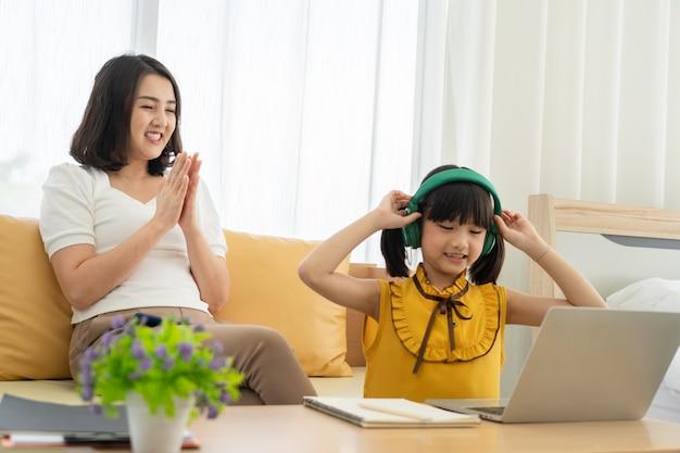 Azjatycka Młoda Matka Z Laptopem Uczy Dzieciaka W Domu Premium Zdjęcia