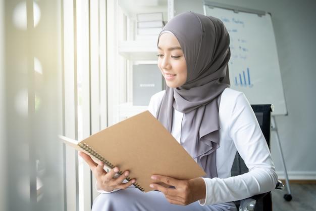 Azjatycka Muzułmańska Kobieta Czyta Książkę W Biurze. Koncepcja Współczesnego Stylu życia Muzułmanów, Portret Muzułmanina. Premium Zdjęcia