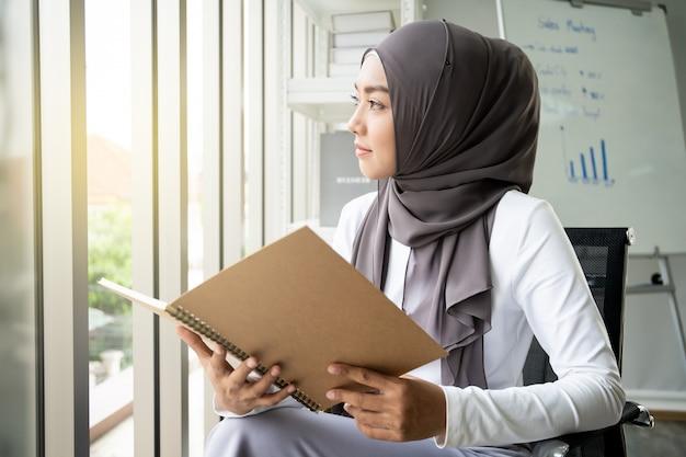 Azjatycka Muzułmańska Kobieta Czyta Książkę W Biurze. Współczesny Styl życia Muzułmanów, Portret Muzułmanina. Premium Zdjęcia