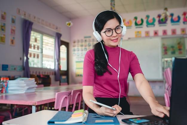 Azjatycka Nauczycielka Przedszkolna Uczy Uczniów W Przedszkolu Online. Nauczyciele I Uczniowie Używają Internetowych Systemów Wideokonferencyjnych Do Nauczania Uczniów. Premium Zdjęcia