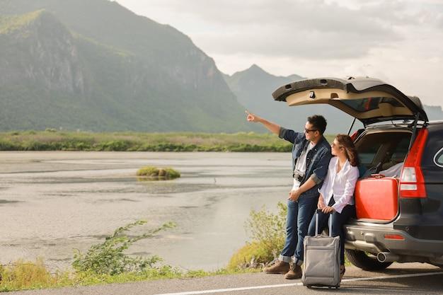 Azjatycka para mężczyzna z rocznika kamerą i kobiety obsiadaniem z tyłu samochodowej podróży góra i jezioro w wakacje z samochodową wycieczką samochodową Premium Zdjęcia
