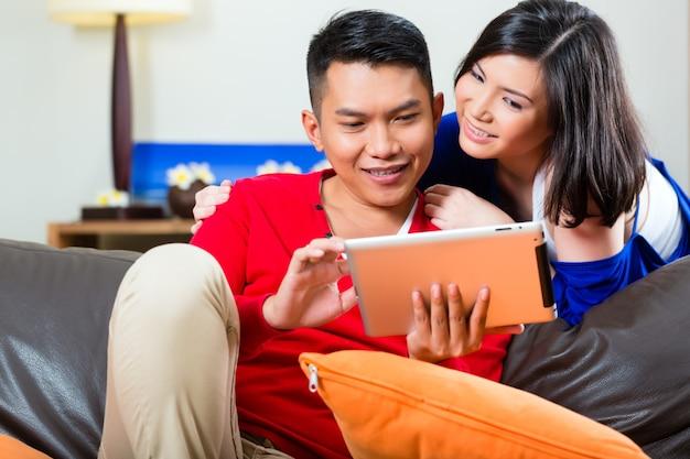 Azjatycka para na leżance z pastylka komputerem osobistym Premium Zdjęcia