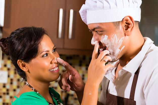 Azjatycka para piec czekoladowego tort w kuchni Premium Zdjęcia