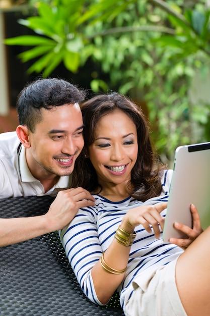 Azjatycka para plenerowa z pastylka komputerem osobistym Premium Zdjęcia