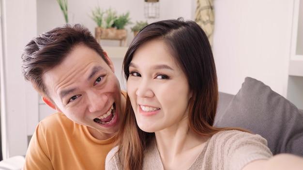 Azjatycka para używa smartphone wideo wezwanie z przyjacielem w żywym pokoju w domu Darmowe Zdjęcia