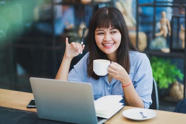 Azjatycka piękna kobieta w błękitnej koszula używać laptop i pijący kawę Premium Zdjęcia