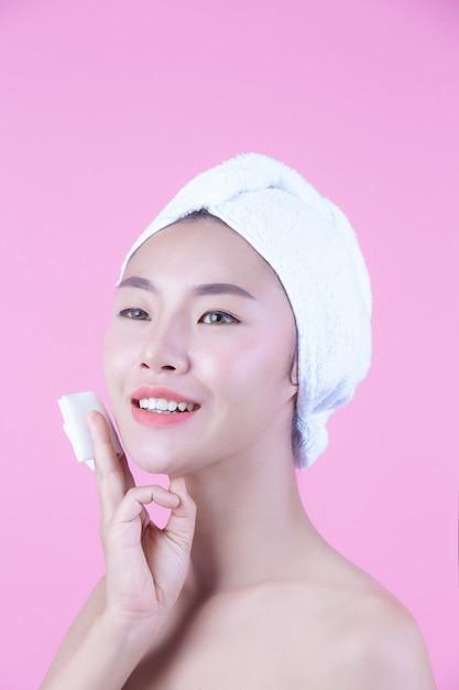 Azjatycka Piękna Kobieta Wyciera Twarz Na Różowym Tle, Kosmetologii I Zdroju. Darmowe Zdjęcia
