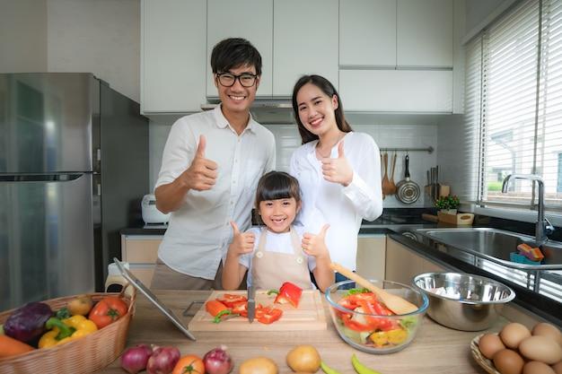 Azjatycka Rodzina Z Ojcem, Matką I Córką Strzępiła Sałatkę Warzywną. Premium Zdjęcia