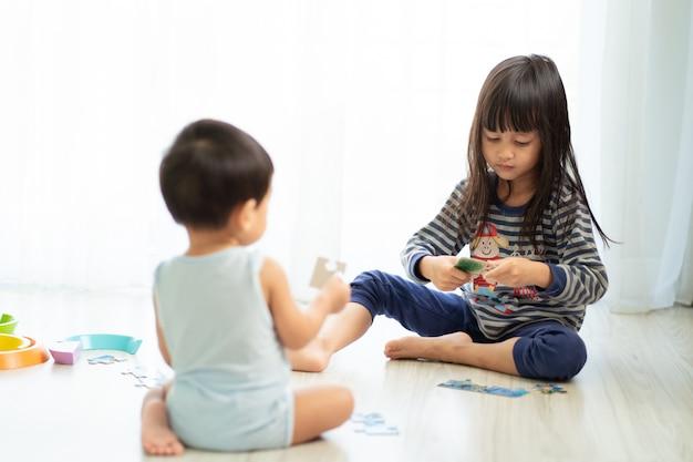 Azjatycka Siostra Gra Puzzle Ze Swoim Młodszym Bratem, Pojęcie Więzi Z Rodzeństwem Premium Zdjęcia