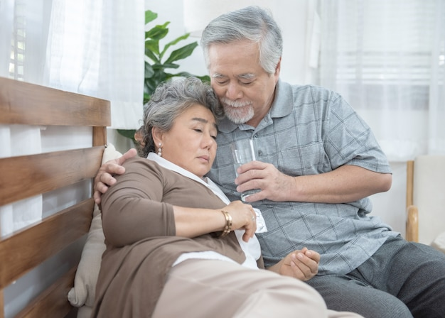Azjatycka Starsza Kobieta Bierze Leki I Wodę Pitną Podczas Gdy Siedzący Na Leżance. Stary Człowiek Dba Jego żony Podczas Gdy Jej Choroba Przy Domem Opieki Zdrowotnej I Medycyny Pojęcie. Premium Zdjęcia