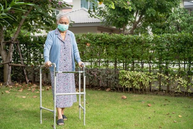 Azjatycka Starsza Kobieta Chodzi Z Chodzikiem I Nosi Maskę Na Twarz W Celu Ochrony Przed Koronawirusem Covid-19. Premium Zdjęcia