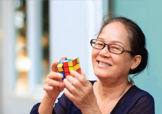 Azjatycka starsza kobieta gra lub rozwiązuje grę kostki rubika. Premium Zdjęcia
