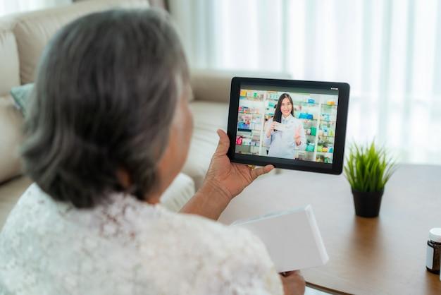 Azjatycka Starsza Kobieta Używa Wideokonferencję, Robi Konsultację Online Z Apteką Konsultując Się Na Temat Choroby I Leków Za Pośrednictwem Połączenia Wideo. Telezdrowie, Telemedycyna I Szpital Online. Premium Zdjęcia