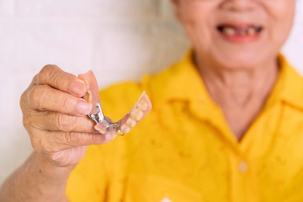 Azjatycka starsza kobieta w wieku powyżej 70 lat powinna się uśmiechać z kilkoma złamanymi zębami i trzymając w ręku protezy. Premium Zdjęcia