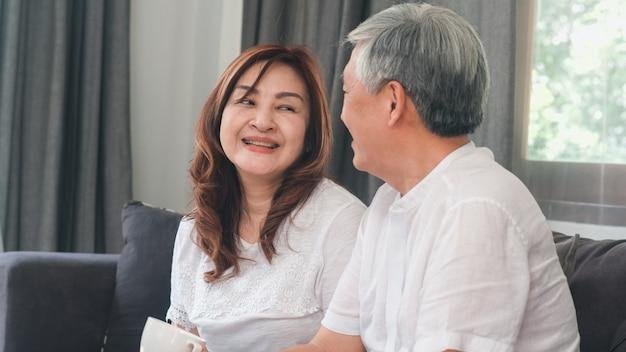 Azjatycka starsza para relaksuje w domu. azjatyccy starsi chińscy dziadkowie, mąż i żona szczęśliwy uśmiech, ściskają opowiadać wpólnie podczas gdy kłamający na kanapie w żywym pokoju pojęciu w domu. Darmowe Zdjęcia