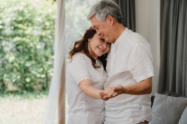 Azjatycka starsza para tańczy razem, słuchając muzyki w salonie w domu, słodka para cieszy się chwilą miłosną podczas zabawy, gdy jest zrelaksowana w domu. styl życia starsza rodzina relaksuje w domu pojęcie. Darmowe Zdjęcia