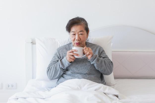 Azjatycka Starsza Stara Kobieta Pije Kawę Lub Herbaty Na łóżku Premium Zdjęcia