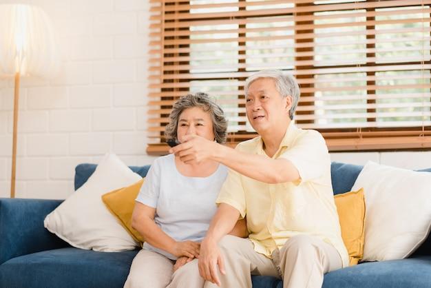 Azjatycka Starszej Osoby Pary Dopatrywania Telewizja W żywym Pokoju W Domu, Słodka Para Cieszy Się Miłość Moment Podczas Gdy Kłamający Na Kanapie Gdy Relaksujący W Domu. Darmowe Zdjęcia