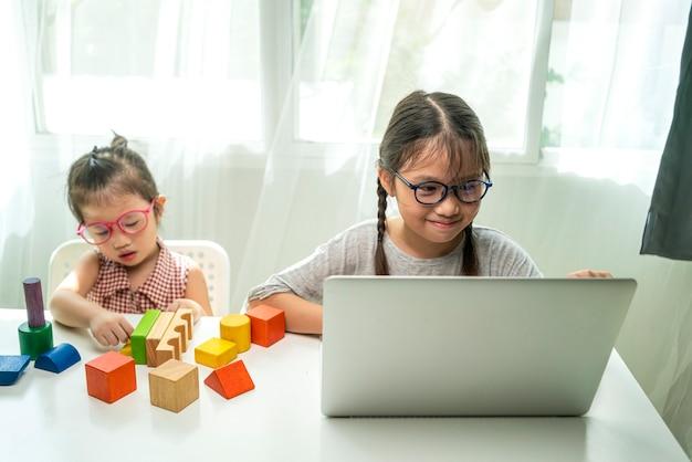 Azjatycka Szczęśliwa Dziewczyna Za Pomocą Laptopa Odrabiania Lekcji I Studiuje Aplikację Online Zoom Ze Swoim Nauczycielem Premium Zdjęcia