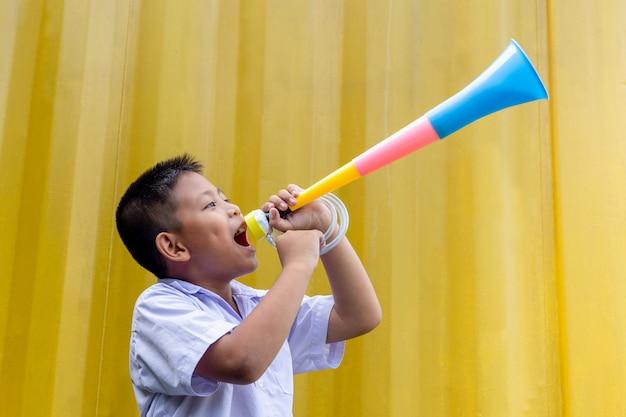 Azjatycka Szkolna Chłopiec Dmucha Kolorowego Róg W żółtym Tle. Premium Zdjęcia