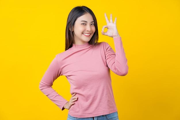 Azjatycka Uśmiechnięta Młoda Kobieta Gestykuluje Ok Szyldowego Dla Zatwierdzenia Lub Zgody Na Odosobnionej Kolor żółty ścianie Premium Zdjęcia