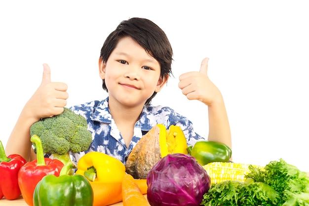 Azjatycka zdrowa chłopiec pokazuje szczęśliwego wyrażenie z rozmaitości świeżym kolorowym warzywem Darmowe Zdjęcia