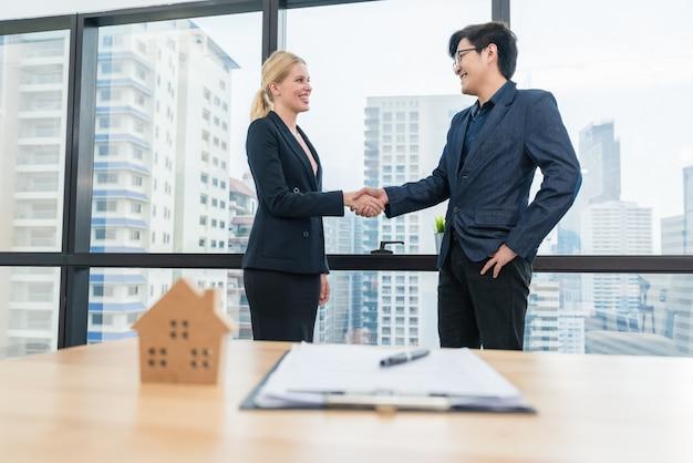 Azjatycki biznes człowiek uścisk dłoni z agentem nieruchomości kobieta po dokonaniu umowy zakupu umowy kredytu mieszkaniowego Premium Zdjęcia