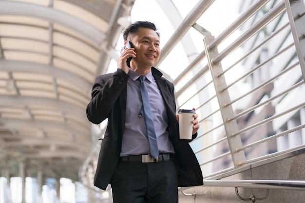 Azjatycki Biznesmen Chodzi I Opowiada Na Telefonie Komórkowym Z Biznesowymi Budynkami Biurowymi W Miasta Tle Premium Zdjęcia